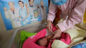 "In this April 25, 2017, photo, a baby receives a vaccine shot next to a poster which reads ""Standardize vaccination and build a healthy China"" at a hospital in Handan in north China's Hebei province. (Chinatopix via AP)"