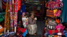 In this July 10, 2018 photo, a vendor at the Witches' Market drinks coffee at her shop full of Andean weavings and embroidery in La Paz, Bolivia. (AP Photo/Juan Karita)