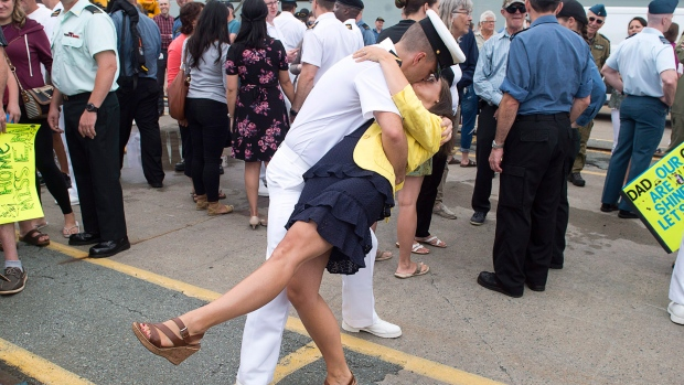 Leading Seaman Daniel Laplante and Melissa Epp kiss on the jetty as HMCS St. John's, one of Canada's Halifax-class frigates, returns to port in Halifax on Monday, July 23, 2018.  (THE CANADIAN PRESS/Andrew Vaughan)