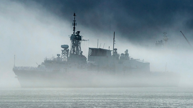 HMCS St. John's, one of Canada's Halifax-class frigates, heads through the fog as it returns to port in Halifax on Monday, July 23, 2018. (THE CANADIAN PRESS/Andrew Vaughan)