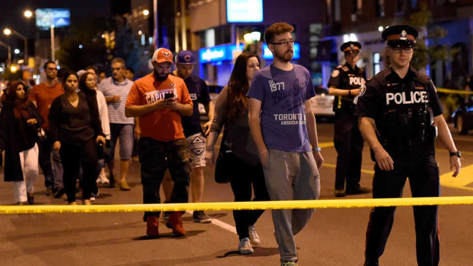 Civilians are escorted from the scene of a mass casualty incident in Toronto on Sunday, July 22, 2018. THE CANADIAN PRESS/Nathan Denette