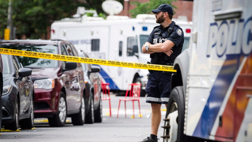 Police watch the perimeter of the scene of a mass shooting in Toronto on Monday, July 23, 2018. THE CANADIAN PRESS/Christopher Katsarov