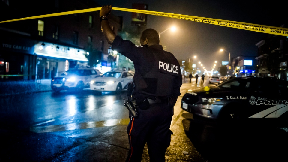 A police officer lifts police tape near the scene of a shooting in east Toronto, on Monday, July 23, 2018. (THE CANADIAN PRESS / Christopher Katsarov)