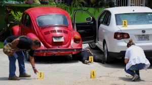 Forensics place numbers by evidence near the body of a woman who was found dead between two cars parked outside a restaurant in Acapulco, Mexico, Sunday, July 22, 2018. (AP Photo/Bernandino Hernandez)