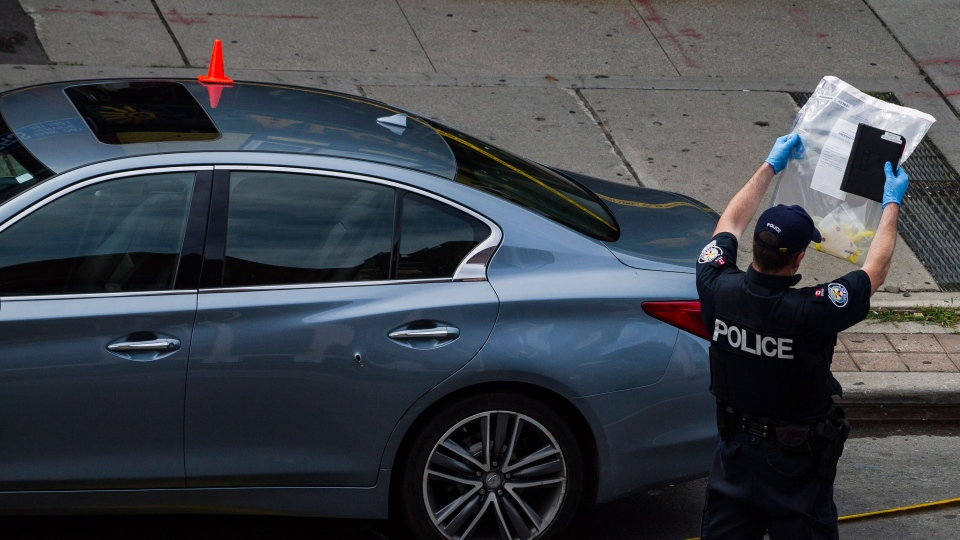 Police are photographed investigating a car with a bullet hole within the scene of a mass shooting in Toronto on Monday, July 23, 2018. THE CANADIAN PRESS/Christopher Katsarov