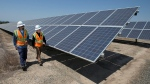 In this Aug. 17, 2017, file photo, Solar Tech Joshua Valdez, left, and Senior Plant Manager Tim Wisdom walk past solar panels at a Pacific Gas and Electric Solar Plant, in Dixon, Calif. (AP Photo/Rich Pedroncelli)