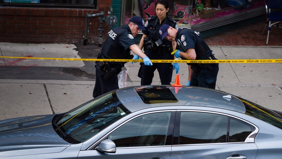 Police investigate a car with a bullet hole within the scene of a shooting in east Toronto, on Monday, July 23, 2018. Police were trying Monday to determine what prompted a 29-year-old man to go on a shooting rampage in a popular Toronto neighbourhood, killing two people and injuring 12 others. THE CANADIAN PRESS/Christopher Katsarov