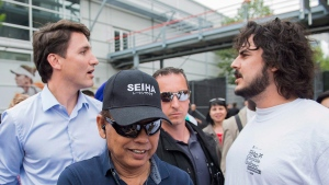 Prime Minister Justin Trudeau, left, is confronted by a man during a visit to a Saint-Jean Baptiste day celebration in Montreal, Saturday, June 23, 2018. (THE CANADIAN PRESS/Graham Hughes)