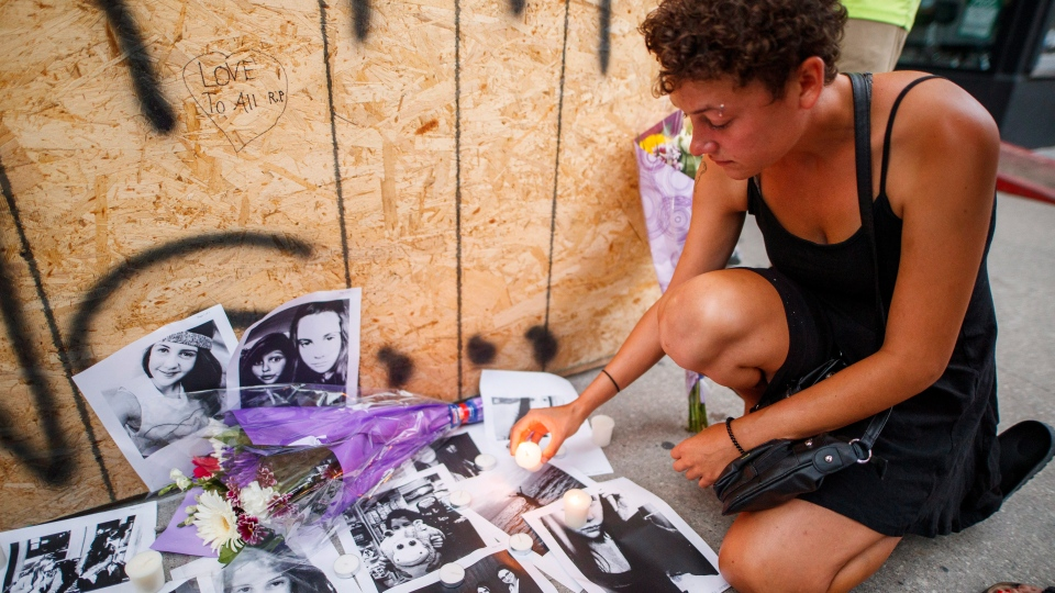 Friend of 18-year-old shooting victim Reese Fallon, Desirae Shapiro 19, leaves a candle on pictures at a makeshift memorial remembering the victims on Danforth, Ave. in Toronto on Monday, July 23, 2018. (THE CANADIAN PRESS/Mark Blinch)