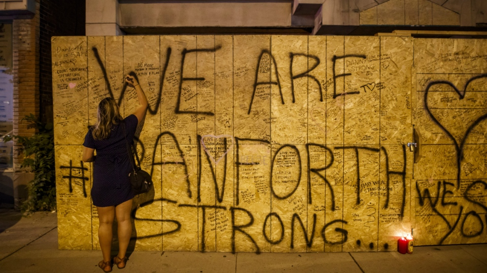 A woman writes a messages on a building under renovation, remembering the victims of a shooting on Sunday evening on Danforth, Ave. in Toronto on Monday, July 23, 2018. THE CANADIAN PRESS/Mark Blinch