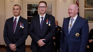 Australian members of the Thai cave rescue team, Craig Challen, left, and Dr. Richard Harris, center, stand with Australia's Governor-General Peter Cosgrove at a function at Government House in Canberra, Australia, Tuesday, July 24, 2018. (Sean Davey/AAP Image via AP)