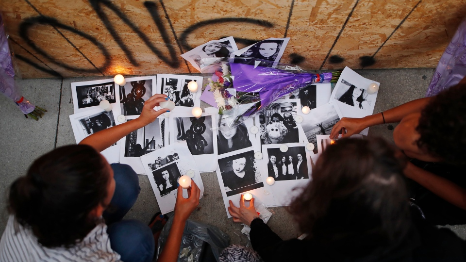 People light candles and leave photos of 18-year-old victim Reese Fallon at a memorial remembering the victims of a shooting on Sunday evening on Danforth, Ave. in Toronto on Monday, July 23, 2018. THE CANADIAN PRESS/Mark Blinch