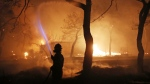 A firefighter sprays water on the fire in the town of Mati, east of Athens, Monday, July 23, 2018. (AP Photo/Thanassis Stavrakis)
