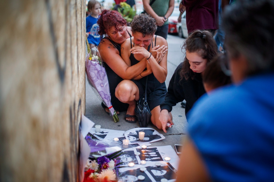 Friends of 18-year-old Danforth shooting victim Reese Fallon, Desirae Shapiro 19, right, and her mother Gina Shapiro, left, react after visiting a makeshift memorial remembering the victims of a shooting on Sunday evening on Danforth, Ave. in Toronto on Monday, July 23, 2018. THE CANADIAN PRESS/Mark Blinch