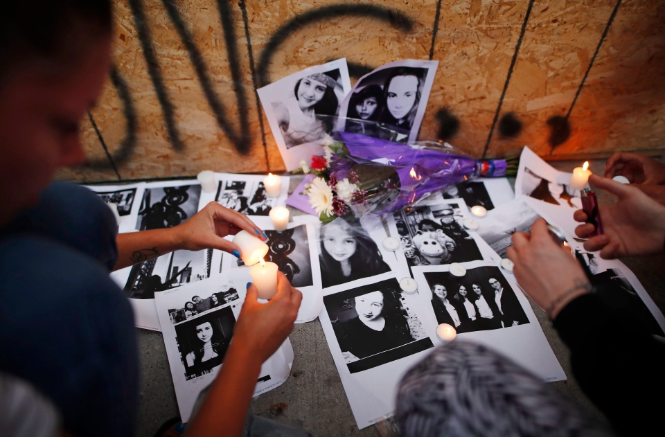 People light candles and leave photos of 18-year-old victim Reese Fallon at a memorial remembering the victims of a shooting on Sunday evening on Danforth, Ave. in Toronto on Monday, July 23, 2018. (THE CANADIAN PRESS/Mark Blinch)