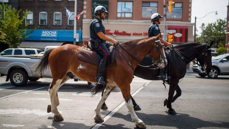 Mounted police patrol Danforth Avenue where a shooting took place on Sunday evening, in Toronto on Tuesday, July 24, 2018. (THE CANADIAN PRESS/Mark Blinch)