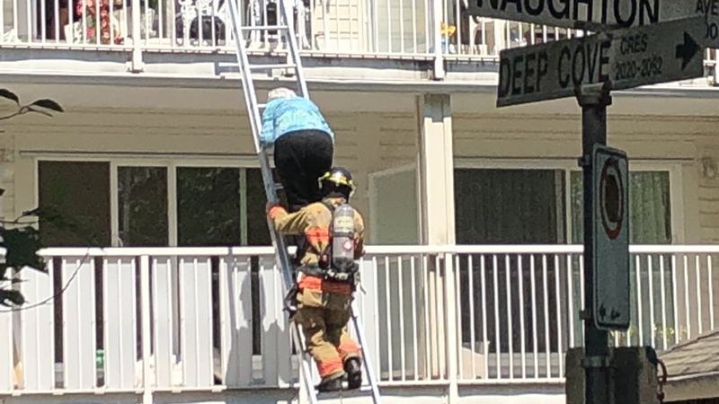 Firefighters help a resident escape a fire that broke out at the Lions Manor seniors' home in North Vancouver on Tuesday. (Twitter/Andrea Simpson)