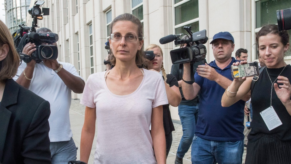 Clare Bronfman, center, is surrounded by reporters as she leaves Federal court, Tuesday, July 24, 2018, in the Brooklyn borough of New York. (AP Photo/Mary Altaffer)