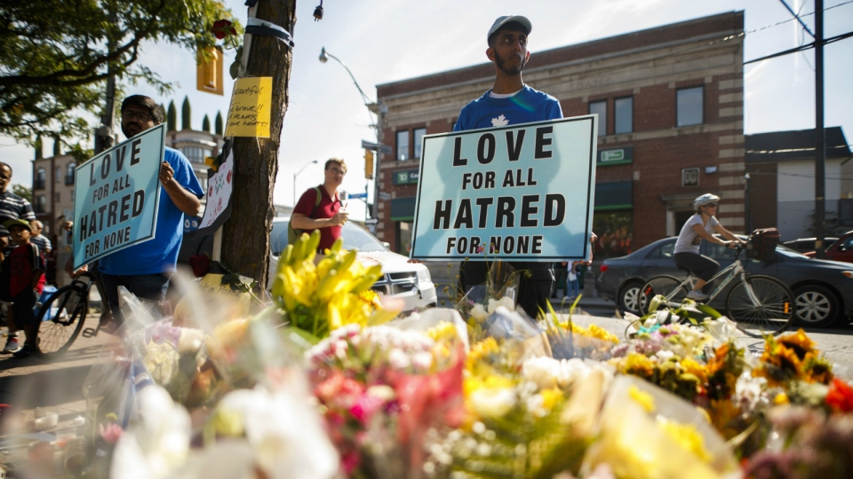 A man holds a sign reading 'Love for All Hatred of None' at a memorial remembering the victims of a shooting on Sunday evening on Danforth, Avenue in Toronto on Tuesday, July 24, 2018. THE CANADIAN PRESS/Mark Blinch