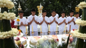 Soccer coach Ekkapol Janthawong, left, and members of the rescued soccer team attend a Buddhist ceremony believed to extend the lives of its attendees as well as ridding them of dangers and misfortunes in the Mae Sai district, Chiang Rai province, northern Thailand, Tuesday, July 24, 2018. (AP Photo/Sakchai Lalit)