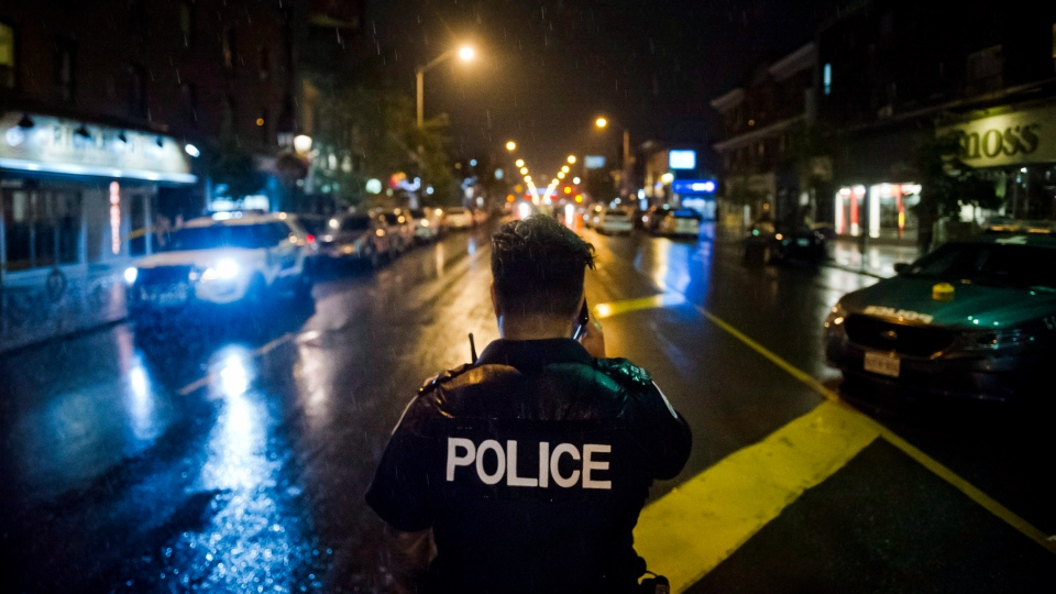 Police are seen around the scene of a shooting in east Toronto, on Monday, July 23, 2018. The parents of Faisal Hussain, whose shooting spree Sunday in Toronto's Greektown left two people dead and 13 injured, say their son had struggled all his life with psychosis and depression, but none of the medications or therapies he tried were able to overcome his mental illness. THE CANADIAN PRESS/Christopher Katsarov