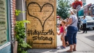 People write messages on a makeshift memorial remembering the victims of a shooting on Sunday evening on Danforth Avenue, in Toronto on Tuesday, July 24, 2018. THE CANADIAN PRESS/Mark Blinch