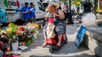 A woman reacts at a memorial honouring the victims of a shooting on Sunday evening on Danforth Avenue, in Toronto on Tuesday, July 24, 2018. THE CANADIAN PRESS/Mark Blinch