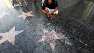 Victor Lomelli of Los Angeles blogs over the vandalized star of Donald Trump on the Hollywood Walk of Fame Wednesday morning, July 25, 2018, in Los Angeles. (AP / Reed Saxon)