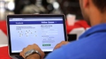 FILE - In this Thursday, Jan. 4, 2018 file photo, a man enters his Facebook page at a restaurant in Brasilia, Brazil. (AP Photo/Eraldo Peres, File)