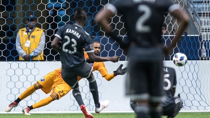 Vancouver Whitecaps' Kei Kamara, front left, scores on a penalty kick against Montreal Impact goalkeeper Clement Diop during second half semifinal Canadian Championship soccer action in Vancouver on Wednesday July 25, 2018. THE CANADIAN PRESS/Darryl Dyck