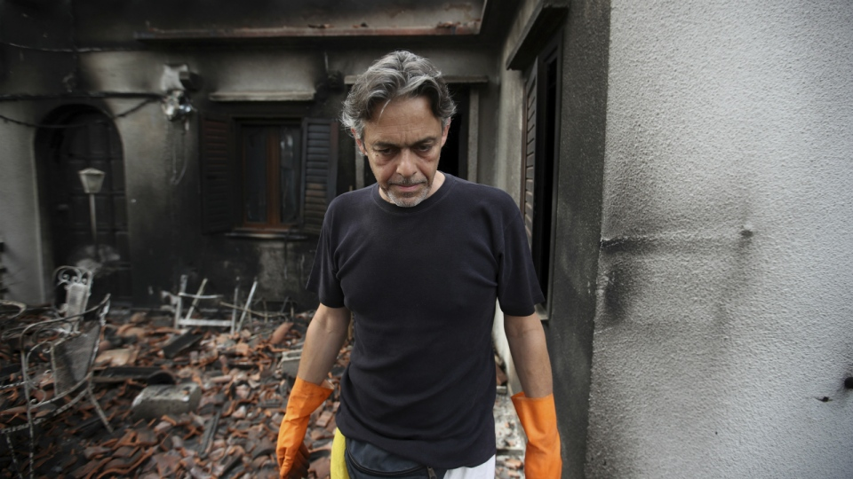 Girogos Handrinos stands outside his burned house in Mati, east of Athens, Thursday, July 26, 2018. (AP Photo/Thanassis Stavrakis)