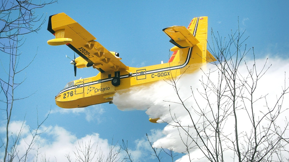 In this 2013 file photo, a Bombardier 415 water bomber operating out Ontario dumps a load water on a fire along East Beauregard Lake Road Wednesday afternoon, May 15, 2013 near Barnes, Wis. (AP Photo/The Duluth News-Tribune, Bob King)