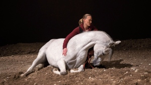 """Cavalia"" horse trainer and rider Elise Verdoncq lies with an Arabian Horse named ""Frosty"" in the arena under the white top in Toronto as preparations continue on Thursday, March 26, 2015 to open the Odysseo show on April 8. THE CANADIAN PRESS/Chris Young"
