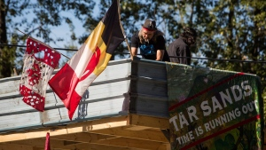 A man known as Blackwolf secures an American Indian Movement flag at Camp Cloud near the entrance of the Kinder Morgan Trans Mountain pipeline facility in Burnaby, B.C., on Saturday July 21, 2018. THE CANADIAN PRESS/Ben Nelms