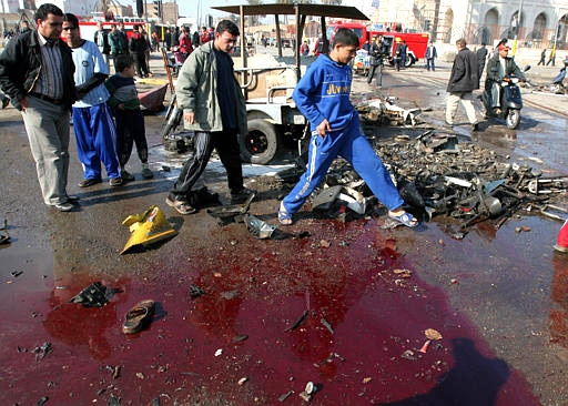 People walk past a pool of blood at Bab al-Sheik market in central Baghdad, Iraq on Tuesday. (AP / Karim Kadim)