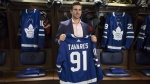 John Tavares holds up a jersey bearing his name in the Maple Leafs' locker room following a news conference in Toronto after signing with the Toronto Maple Leafs on July 1, 2018. (THE CANADIAN PRESS/Chris Young)