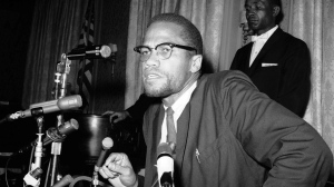 In this Feb. 13, 1963 file photo, Nation of Islam leader Malcolm X speaks to the press in New York as Muslims were picketing through the Times Square area. (Marty Lederhandler/ AP Brown)