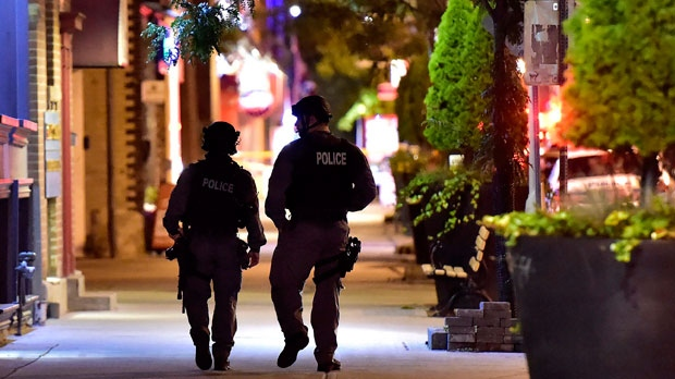 Tactical police officers walk along Danforth Avenue at the scene of a mass shooting in Toronto on Sunday, July 22, 2018. THE CANADIAN PRESS/Frank Gunn