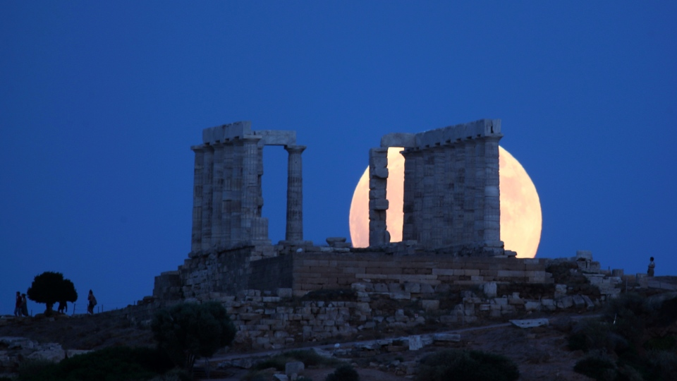 A full moon rises behind the ancient temple of Poseidon in cape Sounio, about 65 kilometers (40miles) south of Athens, Friday, July 27, 2018. (AP Photo/Thanassis Stavrakis)