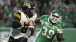 Hamilton Tiger-Cats quarterback Jeremiah Masoli, left, is chased by Saskatchewan Roughriders defensive lineman Charleston Hughes during second half CFL action at Mosaic Stadium in Regina on Thursday, July 5, 2018. (THE CANADIAN PRESS/Mark Taylor)