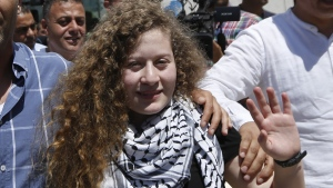 Ahed Tamimi waves after she visited the tomb of former Palestinian leader Yasser Arafat in the West Bank city of Ramallah, on July 29, 2018. (Majdi Mohammed / AP)