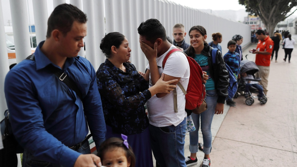 Calet Garcia, centre, of Honduras, cries once he realizes he will be able to apply for asylum in the U.S. with his friend Daisy Avelar, second from left, of El Salvador, on July 26, 2018, near the San Ysidro port of entry in Tijuana, Mexico. (Gregory Bull / AP)