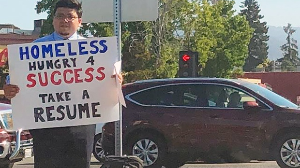 Homeless man holds sign 'Hungry For Success,' hands out resume
