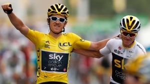 Tour de France winner Britain's Geraint Thomas, left, reacts with Britain's Chris Froome on the Champs Elysees avenue after the twenty-first stage of the Tour de France cycling race in Paris, France, Sunday July 29, 2018. (AP Photo/Laurent Rebours)