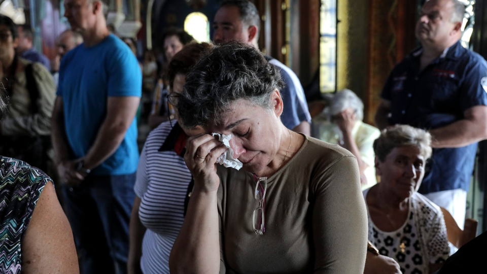 Orthodox faithful attend a memorial service for the victims of a forest fire, inside a church at Mati village, east of Athens, Sunday, July 29, 2018. (AP Photo/Yorgos Karahalis)