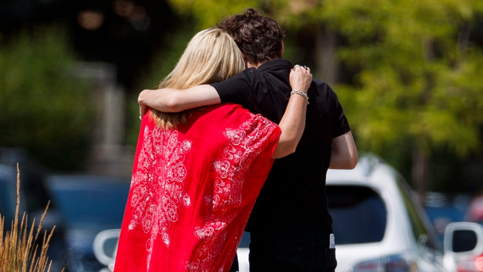 Mourners embrace outside of the public visitation for Reese Fallon at a funeral home in Toronto, Sunday, July 29, 2018. Fallon, 18, was one of two people killed in the mass shooting in Toronto's Greektown neighbourhood last Sunday, July 22. (Mark Blinch/ The Canadian Press)