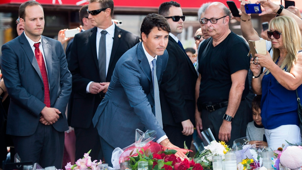 Prime Minister Justin Trudeau, centre, pays his respects and places flowers at the fountain at the Alexander the Great Parkette, near where people were gunned down and injured from the recent Danforth shootings in Toronto on Monday, July 30, 2018. THE CANADIAN PRESS/Nathan Denette