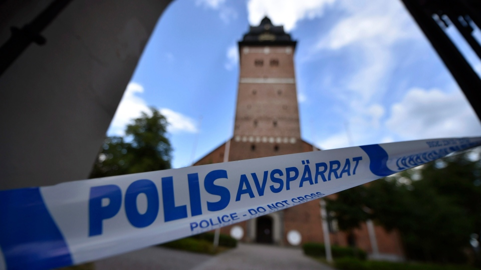 In this Tuesday, July 31, 2018 photo, a police cordon is seen near the scene of a robbery at the Strangnas Cathedral, in Strangnas, Sweden. Police say thieves have stolen priceless treasures from the Swedish royal regalia, including a jeweled crown, from a cathedral where they were on display, before speeding off by motorboat. (Pontus Stenberg/TT News Agency via AP)