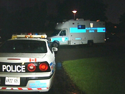 Police vehicles are seen outside Earnscliffe Public School, in Brampton, after a 15-year-old was shot on Friday, June 19, 2009.