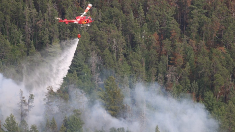 A helicopter drops water on the Parry Sound 33 wildfire on Monday, July 30, 2018. (Ontario Ministry of Natural Resources and Forestry)